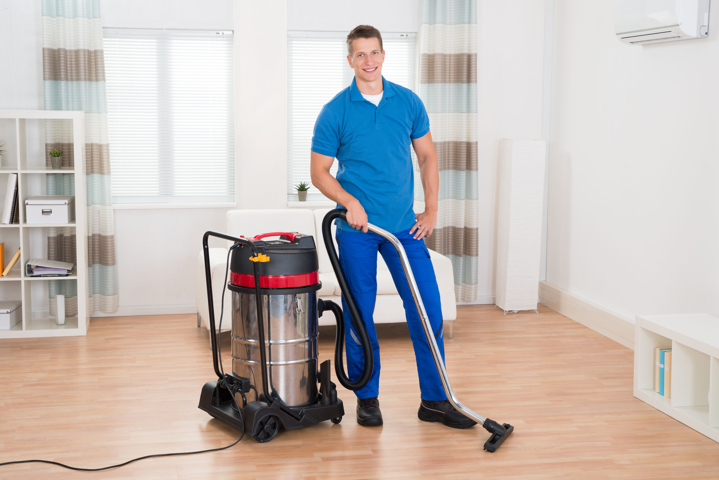 44713918 Happy Male Janitor Vacuuming Wooden Floor In